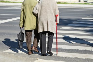 Old couple walks on the pedestrian crossing