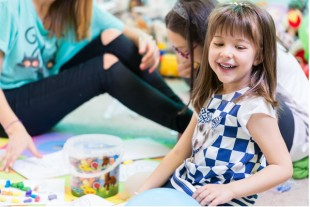 Cheerful pre-school girl wearing a trendy T-shirt while playing