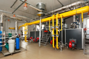 Interior gas boiler with a water treatment system, a lot of boilers, pipes and sensors.