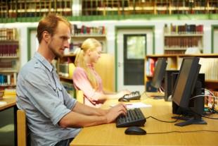 Zwei Studenten sitzen in der Bibliothek am Computer