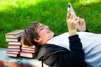Un adolescent joue à la tablette, adossé à des livres
