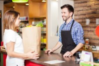 Une cliente à l'épicerie, au magasin, avec un caissier, emballe ses courses
