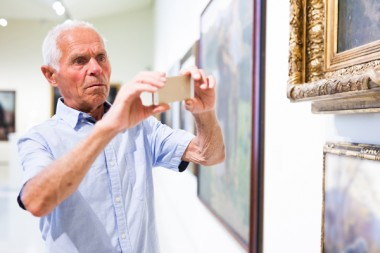 Man photographing painting in museum