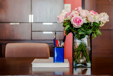 Working table with vase of roses in modern room