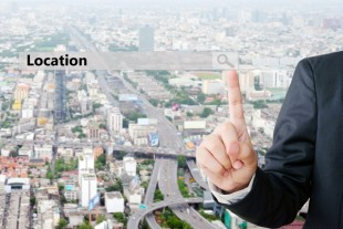 Businessman hand pointing location search bar over blur city scr