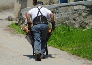 Homme poussant une lourde brouette