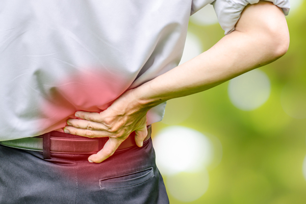 close up of a man holding his back in pain, isolated on white b
