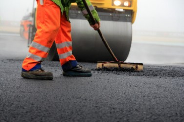 Baustelle: Straßenwalze und Bauarbeiter mit Besen bei der Asphaltfertigung