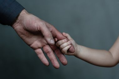 Old man and young girl holding hands together on dark background