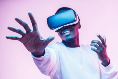 African american man in vr glasses, playing video games with virtual reality headset, trying to touch something with hand