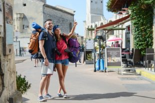 cheerful young couple backpacker traveling and sighseeing in europe during summer