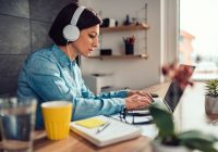 Woman using laptop and listening music on a headphones