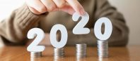 2020 New year saving money and financial planning concept. Female hands putting white number 2020 on stack of coins. Creative idea for business growth, tax payment, investment and banking.