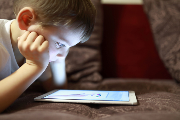 Child with tablet on sofa