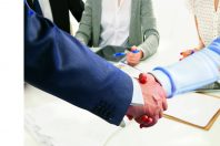 Business meeting at the table shaking hands conclusion of the contract