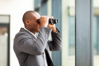 african american businessman using binoculars