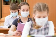 Schoolkids with medicine mask on faces against virus in classroo