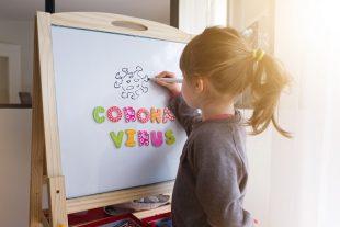 Une fillette dessine le symbole du corona virus sur un tableau blanc