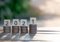 Coins stacks and Text of 2021 number written on wooden blocks on top of coin with sunset nature background, Business and Saving money for new life new year concept, Selective focus.