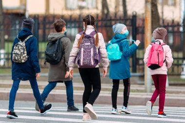 School children cross the road in medical masks. Children go to