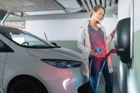 Young woman charging an electric vehicle in an underground garag