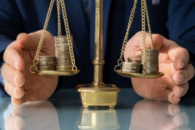 Lawyer's Hand Protecting Justice Scale With Coins