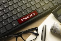 Glasses,pen,book,money, calculator and computer keyboard written with Budget 2022.