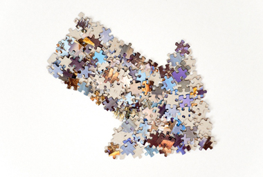 Thick arrow pointing to the left and up, made from plenty of colorful jigsaw puzzle pieces separated on white background.