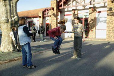 Enfants jouant à l'elastic dans une cours d'école