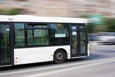 white city bus goes along street