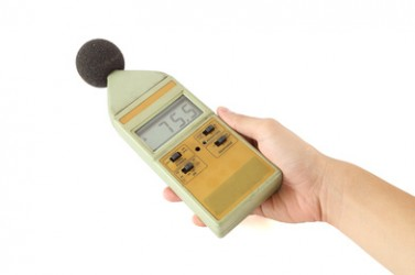 old sound level meter holding on hand