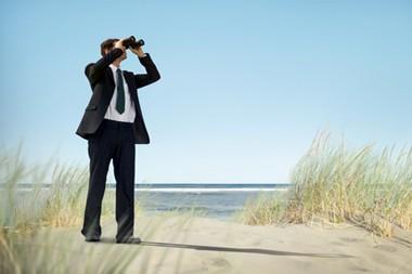 Business Man Holding Spyglass on Beach