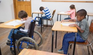 Disabled pupil writing at desk in classroom