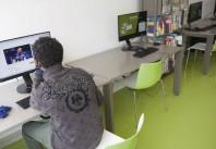 Jeune migrant utilisant le matériel informatique de la médiathèque Don Quichotte de Saint-Denis pour rester en contact avec sa famille.