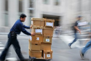 Livreur poussant un chariot avec des cartons