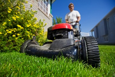 A man mowing the front lawn with focus on the front wheel