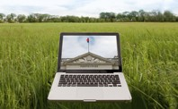 A computer in a field with an image of a city