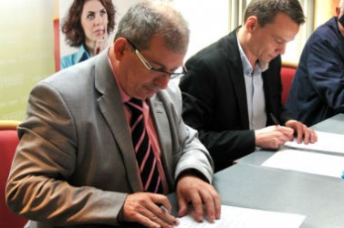 Marc Bury, maire de Petite-Forêt, signant le 21 mai 2015, une convention pour l'achat groupé d'énergie.